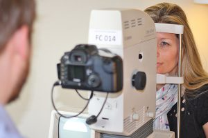 A Screener taking a picture of the back (retina) of a woman's eye